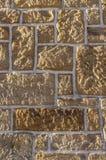 Sandstenvägg, bricked med den olika storleksanpassade vässade lantliga stenen och vita skarvar royaltyfria foton