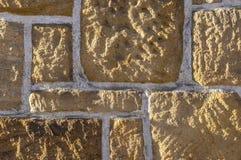 Sandstenvägg, bricked med den olika storleksanpassade vässade lantliga stenen och vita skarvar royaltyfria bilder
