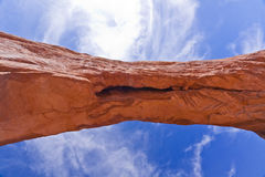 Sandstone Arch against Blue Sky. A sandstone arch stands against a bright blue sky, in the Arches National park of Utah Stock Image