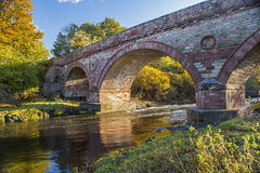 Sandstone arched bridge over a fast river at sunset Stock Image