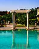 Sandstone arches with pool. Sandstone pillars and a top stone opposite a pool of blue water Royalty Free Stock Photo