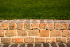 Sandstone brick walkway and grassy hill as a background Stock Images