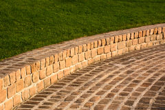Sandstone brick walkway and grassy hill as a background Royalty Free Stock Images