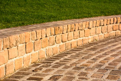 Sandstone brick walkway and grassy hill as a background Stock Photo