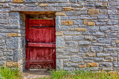 Sandstone Brick Wall and Red Door Backdrop Stock Photos