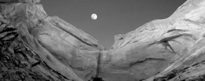 Sandstone cliff & moon royalty free stock photography