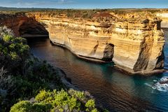 Sun lit sandstone cliffs against the dark ocean at Twelve Apostles, Great Ocean Road, Victoria, Australia. Sandstone cliff with native grasses and shrubs as part royalty free stock photography
