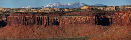 Sandstone cliffs and mountains. Red Wingate sandstone cliffs and the distant La Sal mountains in Indian Creek, Utah Stock Images