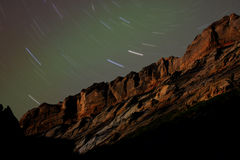 Sandstone Cliffs at Night with Star Trails. A rugged reddish sandstone cliff at night under star trails Royalty Free Stock Image