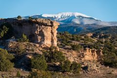 Red rock formation with a snow-capped mountain peak near Santa Fe, New Mexico. Sandstone red rock formation with the snow-capped peak of Santa Fe Baldy in the royalty free stock photos