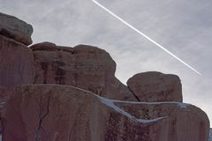 Sandstone Redrock with Clouds Contrail and Snow Patches. Sandstone Redrock Landscape with Snow Patches Cloudy Skies and Airplane Contrail royalty free stock photography