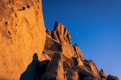Sandstone rock formation, cliff, and boulders glowing orange and gold at sunset under a deep blue sky in Joshua Tree National Park stock images