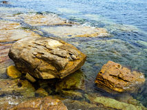 Sandstone Rocks in Ocean. Heavily eroded rocks on an ocean shore, partly covered by high tide Royalty Free Stock Image