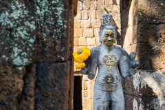 Sandstone statue of god Khmer Art at ancient thai castle or Pras Royalty Free Stock Image