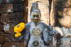 Sandstone statue of god Khmer Art at ancient thai castle or Pras Stock Photos