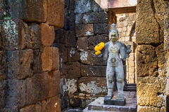 Sandstone statue of god Khmer Art at ancient thai castle or Pras Royalty Free Stock Photo