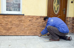 Sandstone tiles. A worker installing new sandstone tiles outside a house. He is measuring a tile with a measuring tape, kneeling on the ground royalty free stock photos