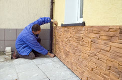 Sandstone tiles. A worker installing new sandstone tiles outside a house. He is measuring the tiles with a measuring tape, kneeling on the ground royalty free stock image