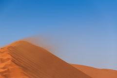 Sandstorm red sand dune Sossusvlei. Sandstorm on edge red sand dune. Sossusvlei, Namibia, Africa Stock Photos