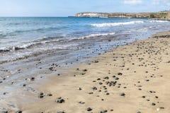 Sandstrand med havsstenar Royaltyfria Foton