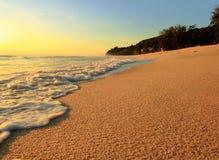 Sandstrand och våg på soluppgång Arkivbild