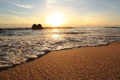 Sandstrand och våg på soluppgång Arkivfoto