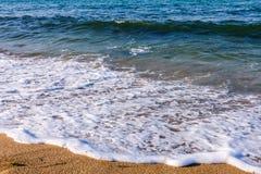 Sandstrand und -welle Stockbild