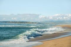 Sandstrand, vågor som bryter till kusten, berg och molnig blå himmel arkivfoton
