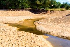 Sandstrandverschmutzung Schwarzwasser im Nebenfluss auf Sand Lizenzfreie Stockbilder