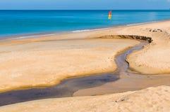 Sandstrandverschmutzung Schwarzwasser im Nebenfluss auf Sand Lizenzfreies Stockfoto