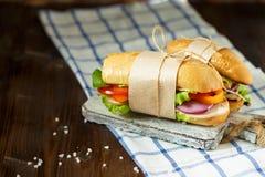 Sanduíche apetitoso do pão friável com galinha, tomates, alface, queijo e especiarias em um fundo de madeira escuro imagem de stock