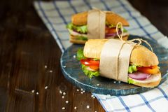 Sanduíche apetitoso do pão friável com galinha, tomates, alface, queijo e especiarias em um fundo de madeira escuro foto de stock royalty free