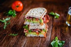 Sanduíche caseiro com bacon, tomate, abacate e verdes fotografia de stock royalty free