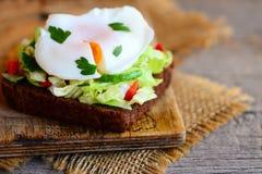 Sanduíche caseiro do brinde do ovo escalfado Um ovo escalfado em uma fatia do pão de centeio com salada de repolho, pepino, pimen fotografia de stock royalty free