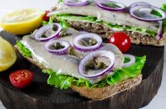 Sanduíche com arenques salgados, manteiga e a cebola vermelha na placa de corte rústica velha Foco seletivo imagens de stock