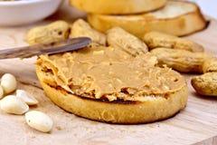 Sanduíche com manteiga e faca de amendoim a bordo Imagens de Stock Royalty Free