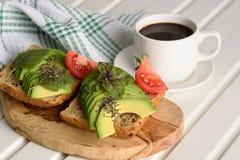 Sanduíche com o copo do abacate e de café - conceito saudável do café da manhã imagens de stock royalty free