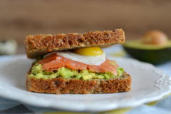 Sanduíche com o ovo do abacate, do salmão fumado e de codorniz Fotografia de Stock Royalty Free