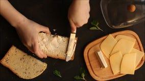 Sanduíche com o pão do queijo espalhado com mãos da manteiga no quadro Alimento snack vídeos de arquivo