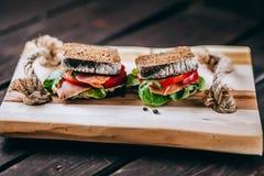 Sanduíche com pão de mistura do centeio, os tomates maduros, os pepinos e os peixes de atum Fotografia de Stock Royalty Free