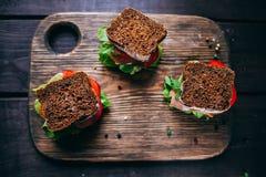 Sanduíche com pão de mistura do centeio, os tomates maduros, os pepinos e os peixes de atum Fotos de Stock Royalty Free