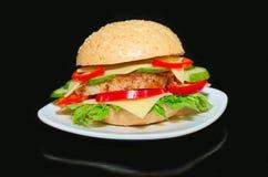 Sanduíche com porco assado, na placa e no fundo preto Imagem de Stock Royalty Free