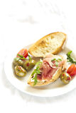 Sanduíche com presunto e azeitonas em uma placa branca imagem de stock royalty free