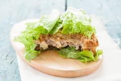 Sanduíche com queijo, presunto e salada em um quadro-negro mordido fora imagem de stock royalty free