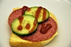 Sanduíche com salame e uma fatia de pepino Foto de Stock
