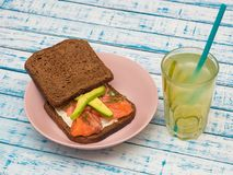 Sanduíche com salmões, abacate, pão preto em uma placa e um vidro da limonada imagens de stock
