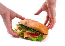 Sanduíche com um presunto, uma paprika e um queijo nas mãos Fotografia de Stock Royalty Free