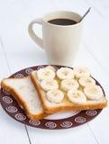 Sanduíche cortado da banana com xícara de café Imagens de Stock
