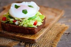 Sanduíche da refeição matinal do ovo escalfado Um ovo escalfado em uma fatia do pão de centeio com couve fresca, pepino, pimenta  fotografia de stock