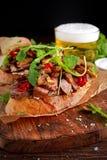 Sanduíche de bife grelhado com cogumelos, manteiga do queijo do ` s da cabra e folhas do rucola na parte superior Cerveja do ouro fotos de stock royalty free